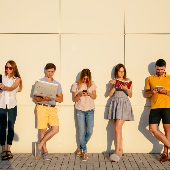 Beautiful young students are using gadgets, reading book and smiling, standing over wall background